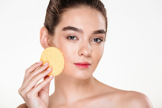 Beauty portrait of young half-naked woman using make-up sponge at her face and looking Free Photo