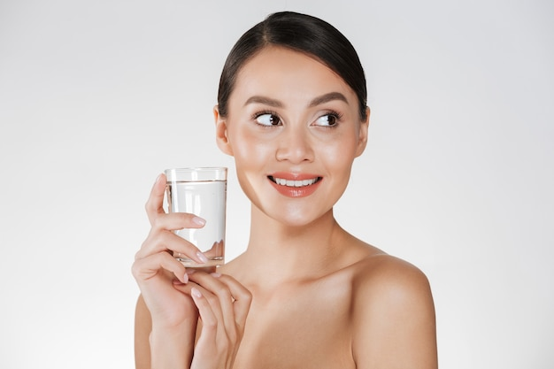 Beauty portrait of young happy woman with hair in bun drinking still water from transparent glass, isolated over white Free Photo