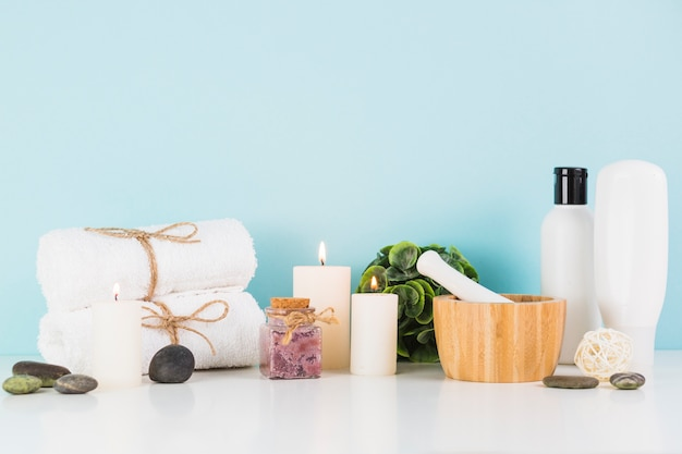 Beauty products with illuminated candles in front of blue wall Free Photo