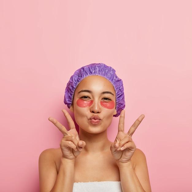 Concetto di bellezza e ringiovanimento. la donna abbastanza coreana fa il gesto della mano di pace, tiene le labbra piegate, ha sotto gli occhi le bende sul viso, indossa un cappello da bagno viola, gode delle procedure termali dopo aver fatto la doccia Foto Gratuite