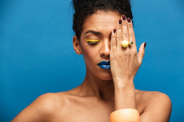 Beauty relaxed mixed-race woman with colorful cosmetics on face posing on camera covering one eye with hand, isolated over blue wall Free Photo