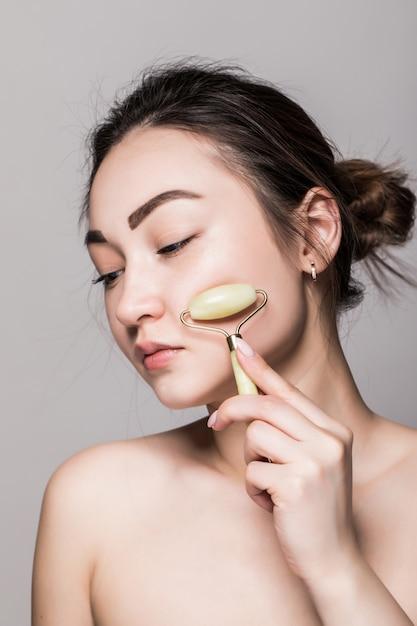 灰色の壁に分離されたフェイシャルマッサージ療法の美容ローズ玉石フェイスローラー。アジアの女性の肖像画。 無料写真