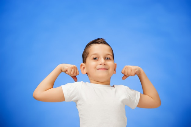 Beauty smiling sport child boy showing his biceps Free Photo
