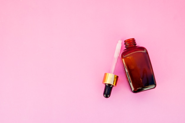 Beauty spa cosmetics, salon therapy . glass bottle on pink . copyspace. Premium Photo
