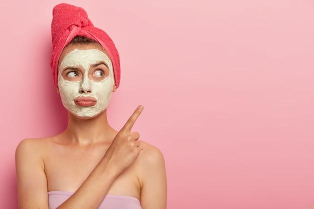 Bellezza, spa, concetto di trattamento. donna infelice insoddisfatta porta le labbra, applica una maschera all'argilla per il ringiovanimento, avvolta in un asciugamano da bagno, punta sullo spazio della copia contro il muro rosa, vuole un risultato veloce Foto Gratuite