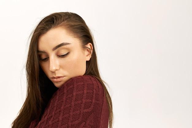 Концепция красоты, стиля и моды. студийный снимок застенчивой красивой молодой женщины с идеальной блестящей кожей, позирующей изолированной в теплом свитере, холодной, с робким выражением лица, смотрящей вниз Бесплатные Фотографии