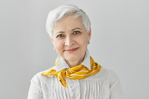 Beauty, style, fashion and aging concept. charming elegant gray haired retired woman wearing stylish yellow silk scarf smiling happily, enjoying her mature age, not being afraid of getting old Free Photo