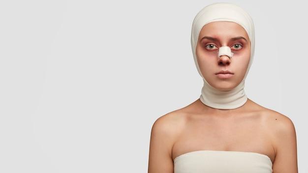 La vittima di bellezza in bende mediche ha un adesivo sul ponte del naso che ha lividi dopo l'operazione Foto Gratuite