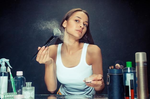 Женщина красоты, применяя макияж. красивая девушка смотрит в зеркало и наносит косметику с большой кистью. кавказская модель в студии Бесплатные Фотографии