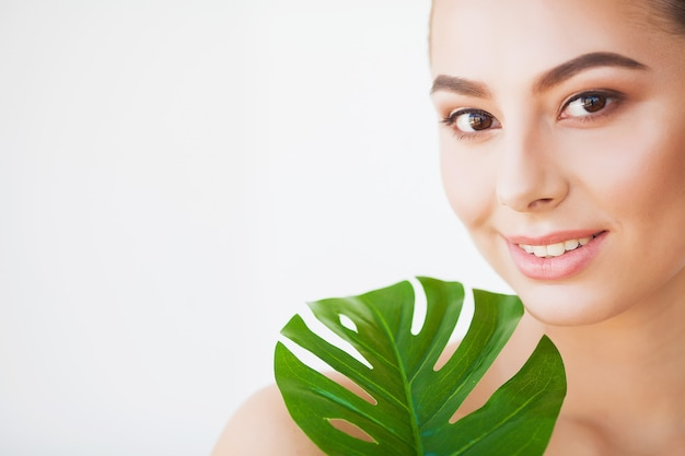 Beauty woman face with healthy skin and green plant Premium Photo