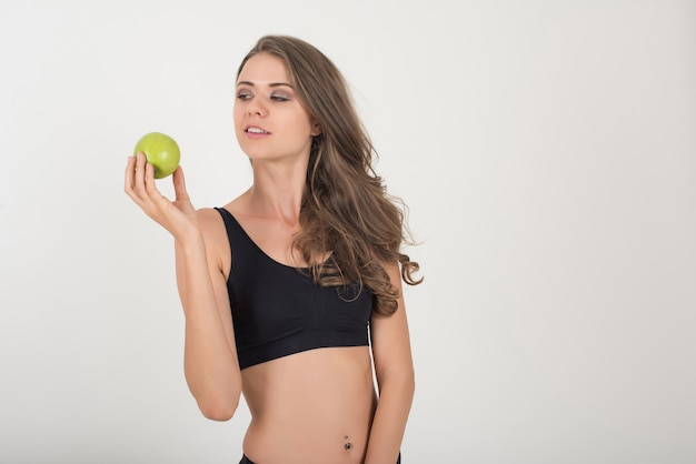 Beauty woman holding green apple while isolated on white Free Photo