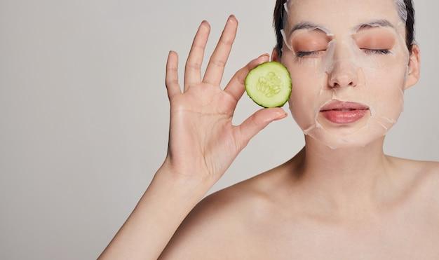 Красавица в увлажняющей маске со свежим огурцом на лице, в серьезном, с закрытыми глазами и руками держит огурцы обеими руками возле ее лица Premium Фотографии