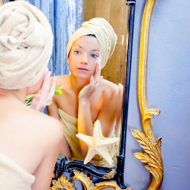 Beauty woman with towel looking at golden mirror Premium Photo