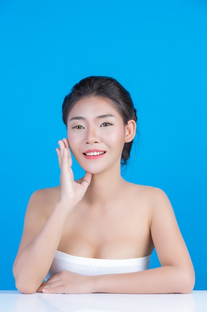 The beauty of women with perfect skin health images touching her face and smiling like a spa to pamper her skin blue Free Photo