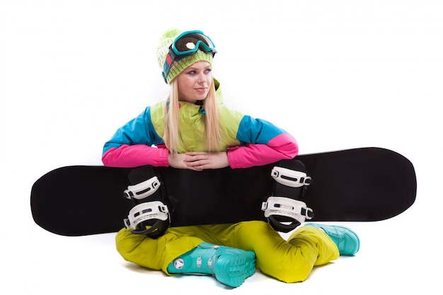 Beauty young woman in ski suit and ski glasses sit with sbowboard Premium Photo