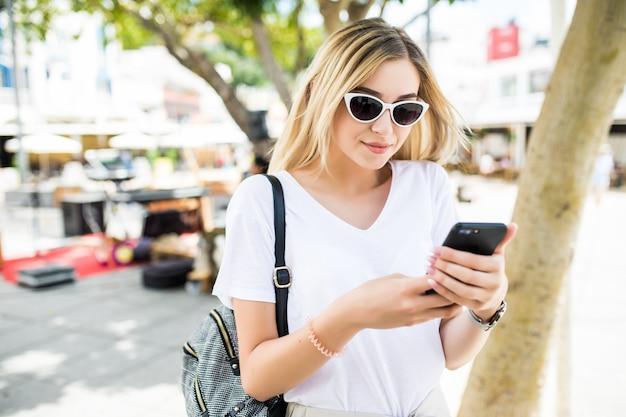 日当たりの良い夏の通りで屋外でスマートフォンを使用して美しい若い女性 無料写真