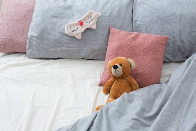 Кровать с мишкой на сером белье Premium Фотографии