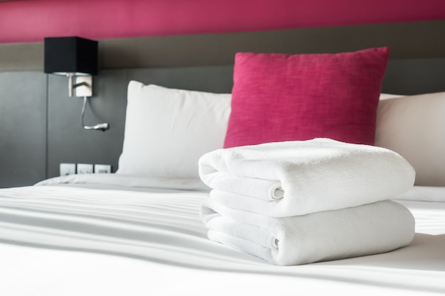 Bed with two white towels and a cushion Free Photo