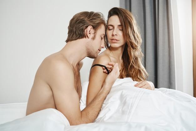 Спальня выстрел красивый бородатый парень, целуя плечо подруги, будучи голым под одеялом. страстные два человека в отношениях, имеющие прелюдию утром, выражая любовь Бесплатные Фотографии