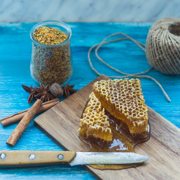 Bee pollens jar; spices and honeycomb piece with knife on chopping board Free Photo