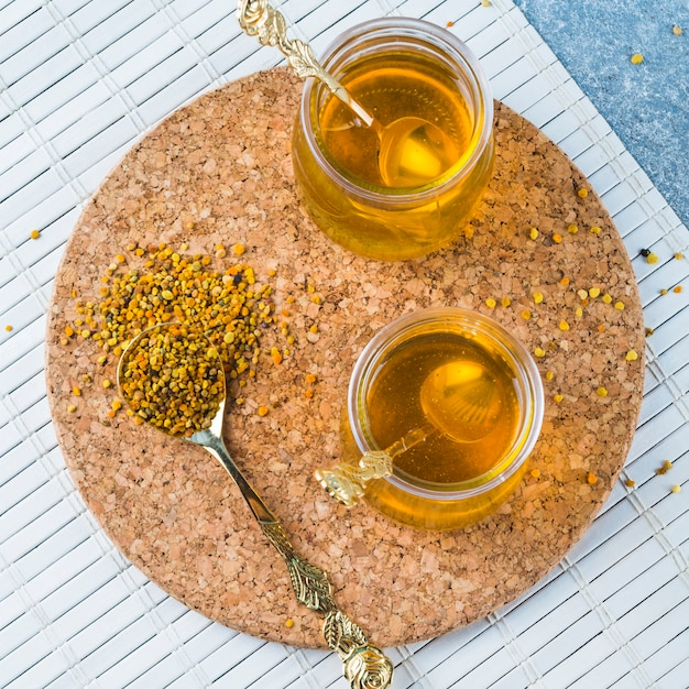 Bee pollens in spoon with honey pots on cork coasters Free Photo