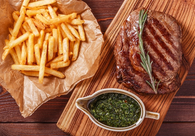 Beef barbecue ribeye steak with chimichurri sauce and french fries Premium Photo