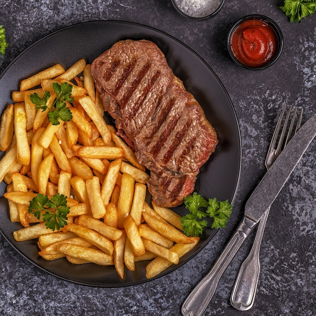 Beef barbecue steak with french fries, top view. Premium Photo