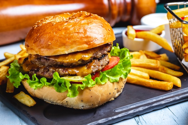 Beef burger meat lettuce tomato cheese french fries side view Free Photo