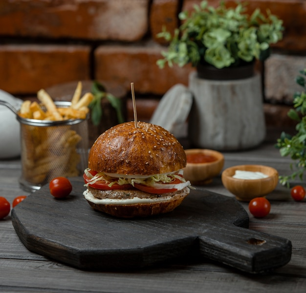 A beef burger stuffed with vegetables and apetizers and served with french fries. Free Photo