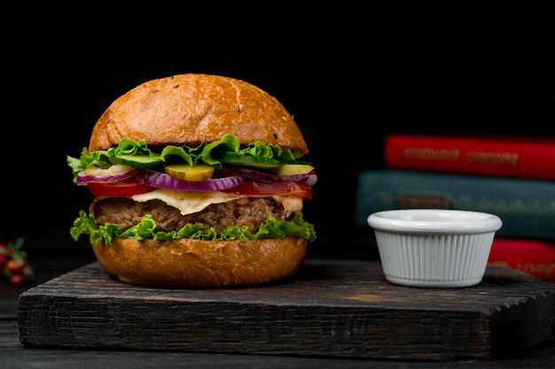 牛肉のコレットバーガー、木の板にソース添え 無料写真