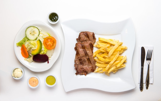 Beef and french fries with salad and creams Premium Photo