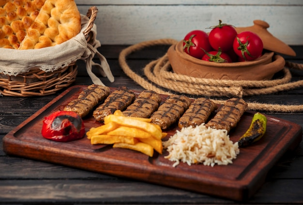 Beef lula kebabs served with rice, fried potatoes, grilled tomato and peppers Free Photo