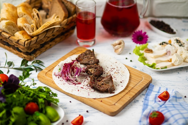 Beef meat kebab with onions, sumakh and lavash on a wooden plate served with wine and vegetables Free Photo