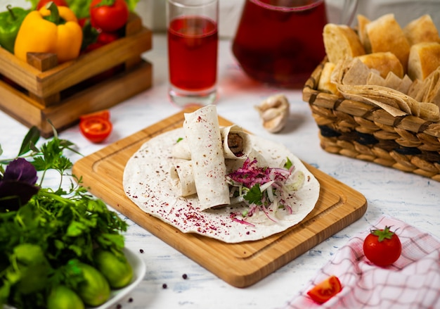 Beef meat traditional turkish kebap durum lavash served on a wooden board with vegetables wine and bread Free Photo