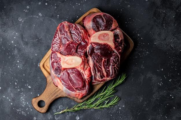 어두운 회색 배경 평면도에 로즈마리와 함께 커팅 보드에 쇠고기 고기 마녀 뼈. 고품질 사진 프리미엄 사진