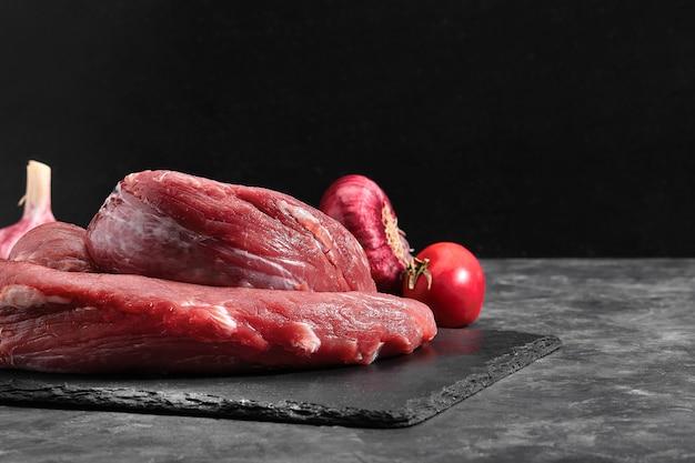 검은 대리석 배경에 쇠고기 원시 등심 안심. 프리미엄 사진