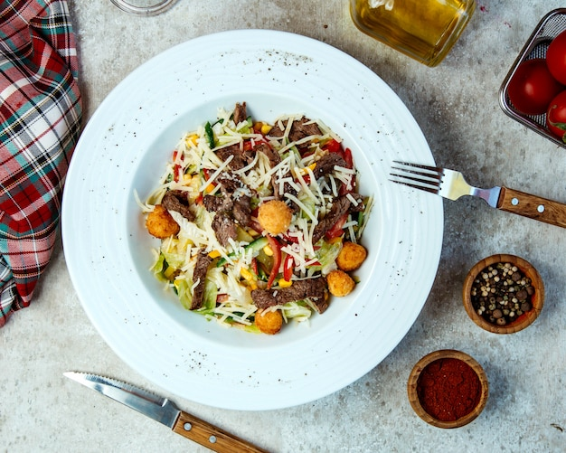 Beef salad with chicken balls, lettuce, grated cheese, corn and bell peppers Free Photo
