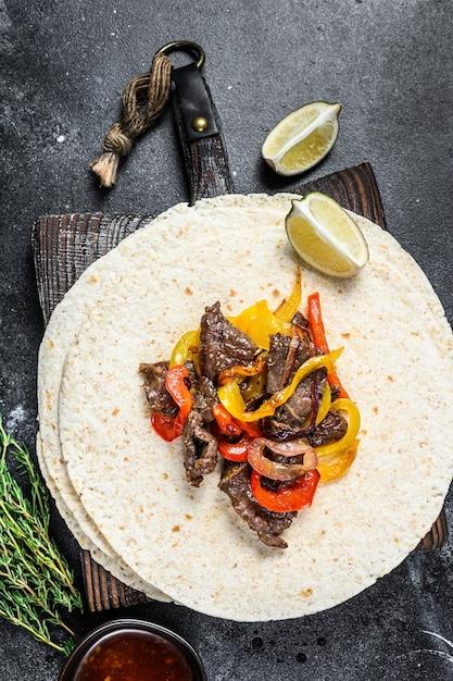 Стейк из говядины фахитас с тортильей, смесью перца и лука традиционные мексиканские блюда Premium Фотографии
