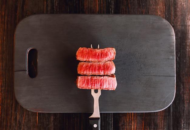 Beef steak on a fork on a dark wooden surface Premium Photo