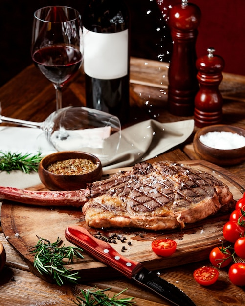 Beef steak garnished with kosher salt on wood serving board Free Photo