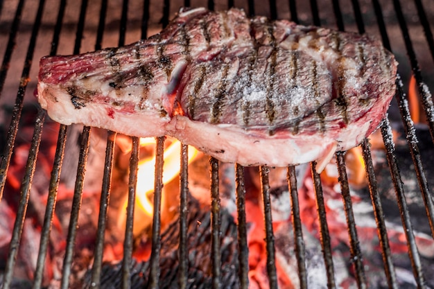 Beef steak on grilled metal sheet over the burning coal Free Photo