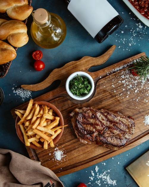 Beef steak served with french fries and diced gren herbs on wooden board Free Photo