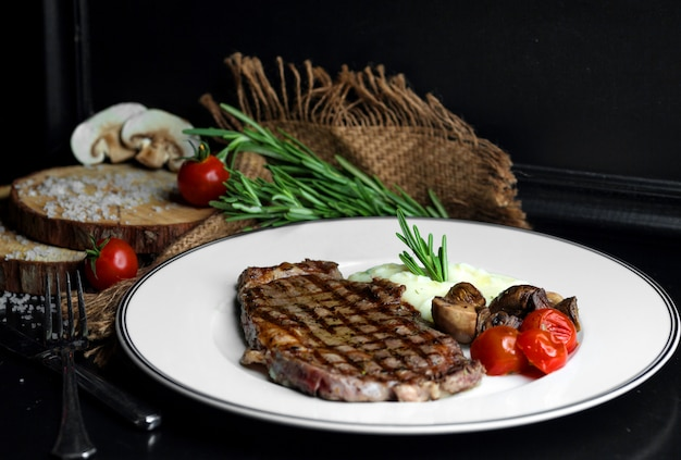 Beef steak served with rice, mushroom and tomato Free Photo
