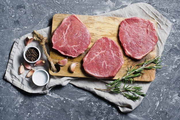 Beef steak tenderloin on a wooden chopping board, garlic and a sprig of rosemary. Premium Photo