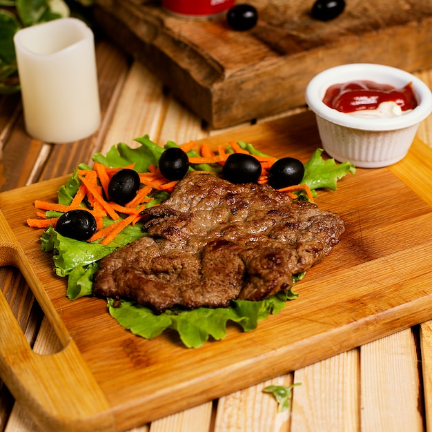 Beef steak thin served with ketchup mayonnaise and vegetable salad. Free Photo