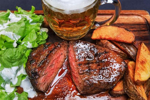 Стейк из говядины с картофелем фри и бокалом пива на деревянной доске Premium Фотографии