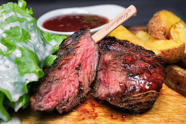 Стейк из говядины с картофелем фри и салатом на деревянной доске Premium Фотографии