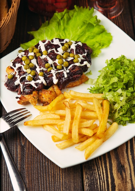 Beef steak with french fries, green salad, green beans and chicken nuggets. Free Photo