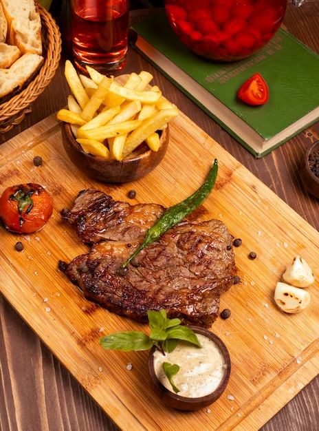 Beef steak with french fries, sour cream mayonnaise sauce and herbs on wooden plate. Free Photo
