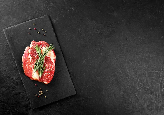 Beef steak with rosemary and pepper on a black table with copy space Premium Photo